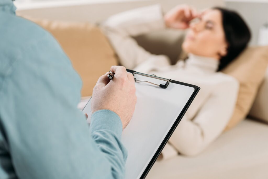 cropped shot of psychotherapist writing on clipboard and young woman lying on couch in office