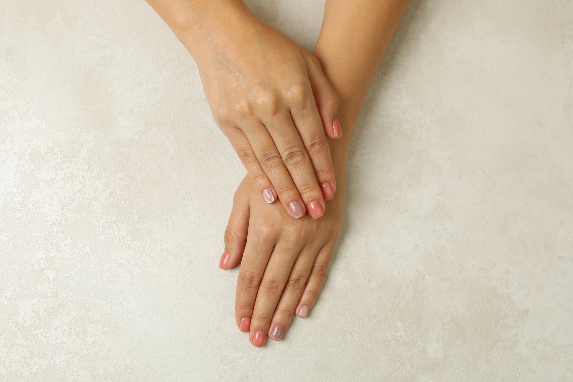 Female hands with pink nails on white background, top view