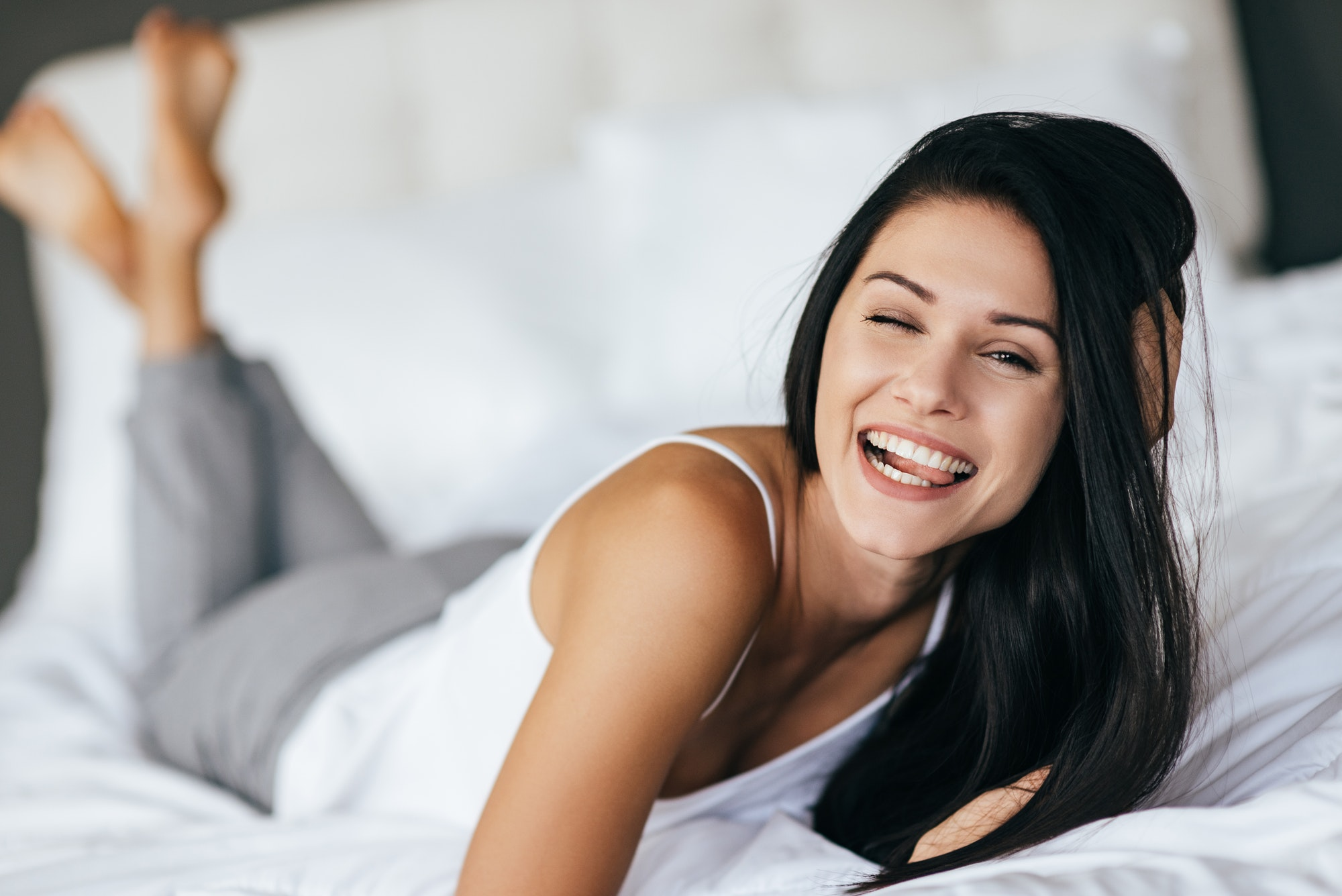 Making a face. Young woman making a face and smiling while lying on the bed at home